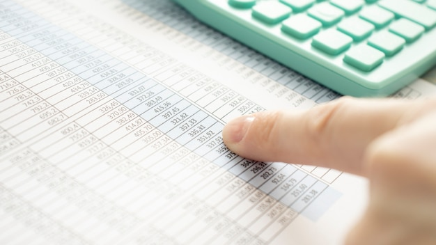 Close up of finger pointing at numbers next to a calculator