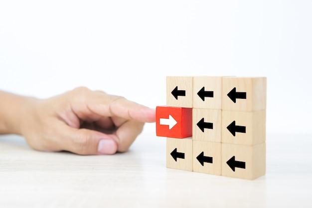 矢印アイコンと積み重ねられた木製のブロックを押すクローズアップ指。