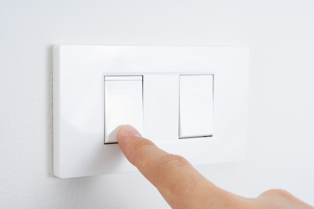 Close up finger turn on or off on white light switch