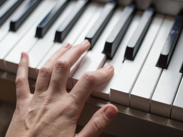 Close up fingers of pianist at the piano keys, arms plays solo of music or new melody. hands of male musician playing at synthesizer.
