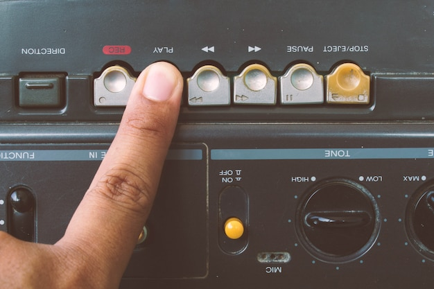 Close up fingers to play radio cassette player,vintage style.