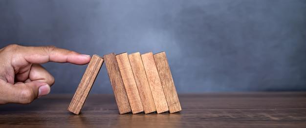 클로즈업 손가락은 나무 블록이 도미노 떨어지는 것을 방지합니다.