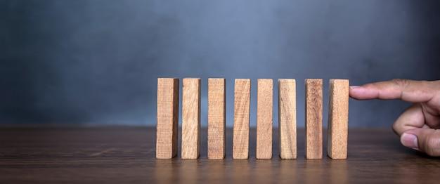 クローズアップの指は、木製のブロックがドミノに落ちるのを防ぎます。