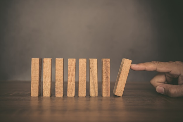 Close up fingers prevent the wooden block from falling domino