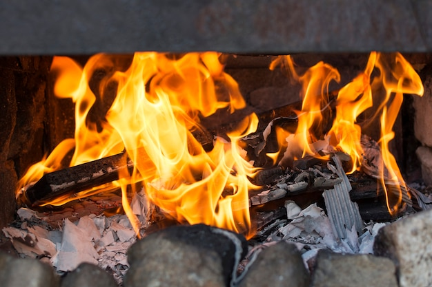 Close up of fire of a barbecue with burned firewood and ashes