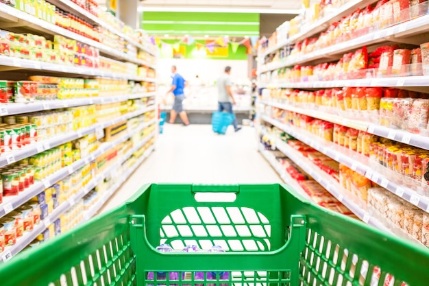 Close up and first person or pov view of a cart buying products and food in a empty supermarket - people buying food in a market