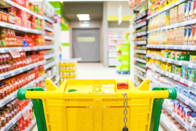 Close up and first person or pov view of a cart buying products and food in a empty supermarket