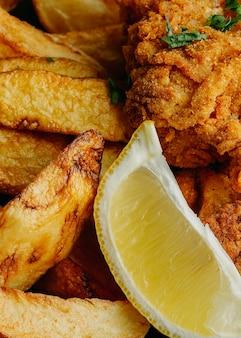 Primo piano di pesce e patatine fritte sulla piastra con fetta di limone