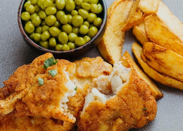 Primo piano di pesce e patatine fritte con piselli