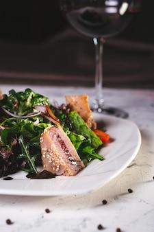 白い皿に緑の魚のサラダをクローズ アップ。