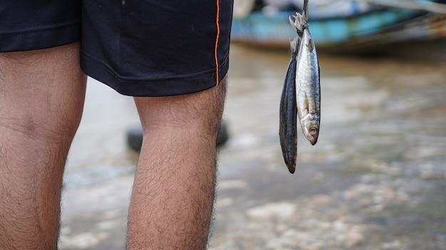 ビーチで彼の釣りから魚を取得する漁師をクローズアップ