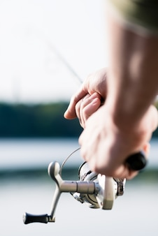 Close-up of fisherman with fishing rod in hand