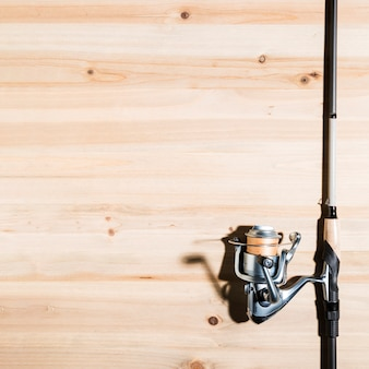 Close-up of fishing rod on wooden desk
