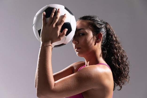 Close-up fit woman holding soccer ball
