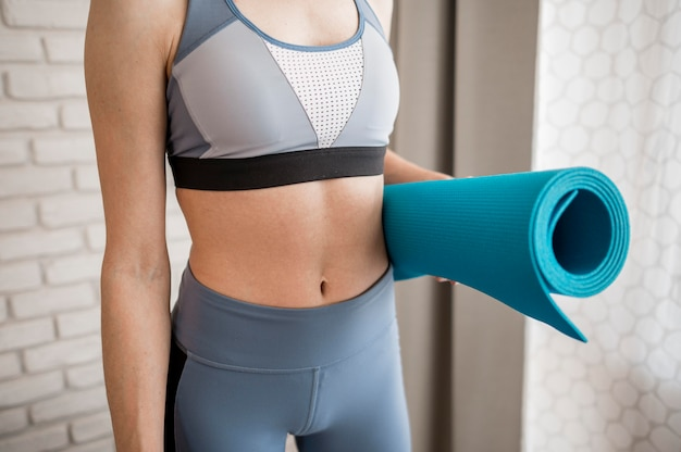 Close-up fit woman holding yoga mat
