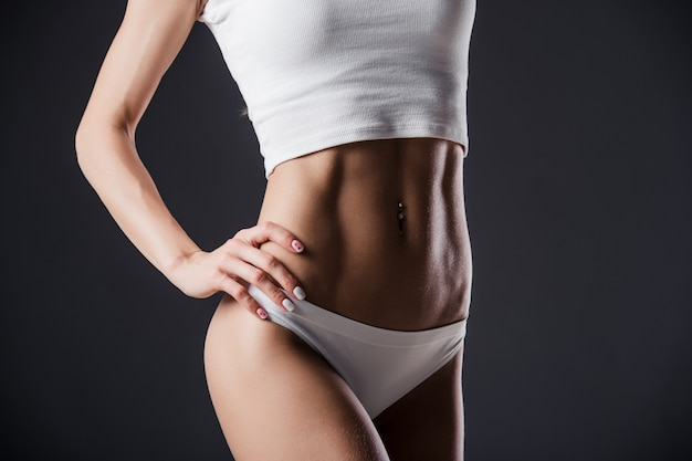 Close up of fit woman's torso with her hands on hips. female with perfect abdomen muscles on black wall