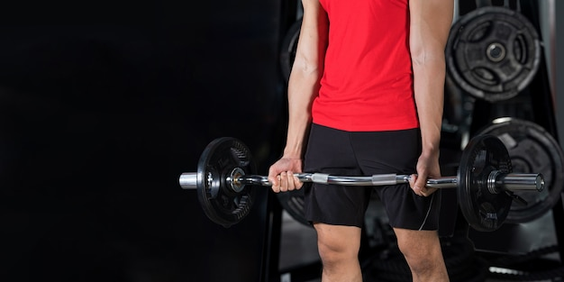Close-up of fitness man, handsome athletic guy workout weight lifting in gym
