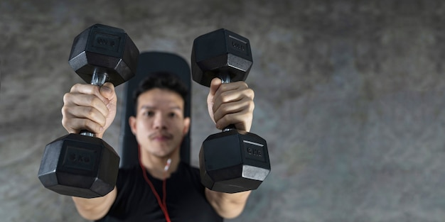 Close-up of fitness man, handsome athletic guy workout with dumbbells,