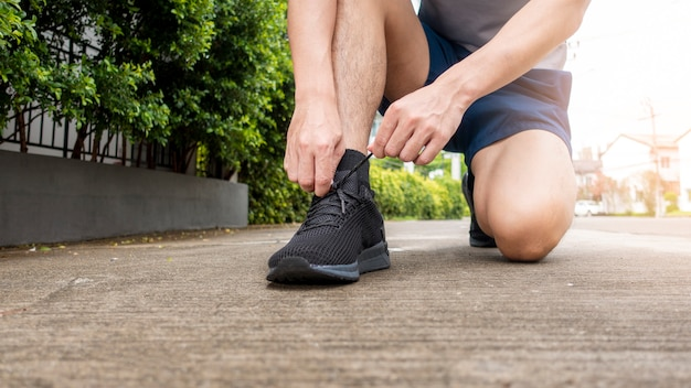 Close up of fitness man is tie shoes