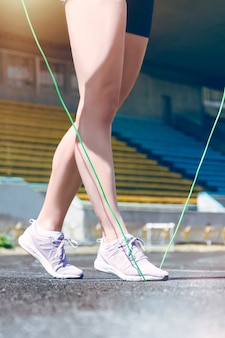 Close up of fitness muscle runner woman legs jumping with jump rope.