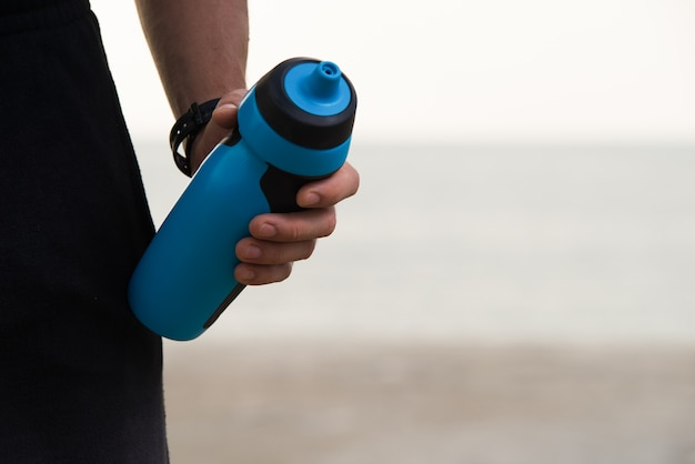 Close-up of fitness shaker bottle in male hand