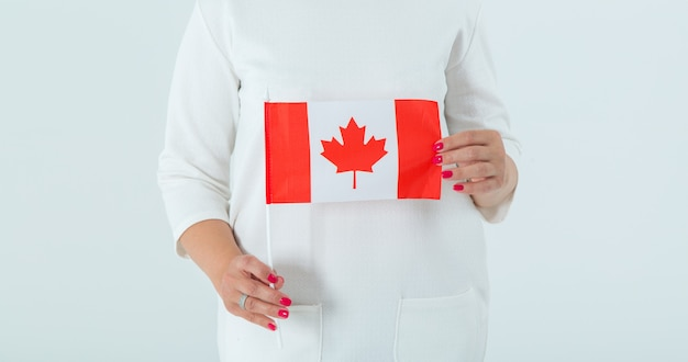 Close-up of the flag of canada in female hands.