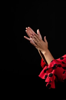Close-up flamenca clapping hands on black background