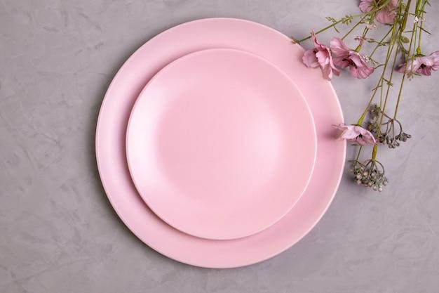 빈 분홍색 접시의 근접 평면 누워 거친 회색 콘크리트에 분홍색 야생화의 장식