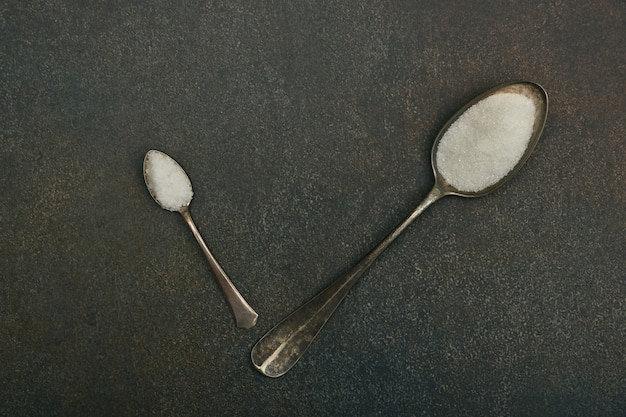 Close up flat lay two vintage metal spoons of white sugar and sea salt on dark grunge stone table surface with copy space, elevated top view, directly above