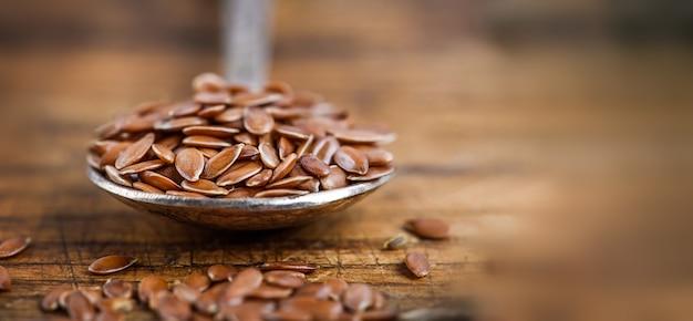 Закройте семя льна в старой ложке, суперпродукт с высоким содержанием клетчатки и противовоспалительных омега-3 жирных кислот.