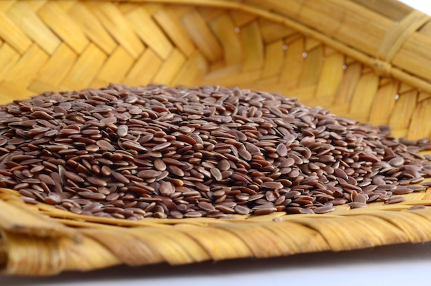 Close up of flax seeds in wooden basket on white surface