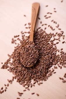 Close up flax seeds in a wooden spoon.