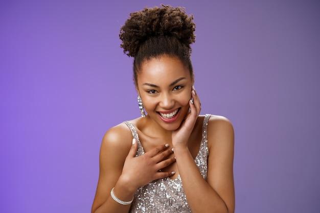 クローズアップの軽薄な生意気な若いスタイリッシュなアフリカ系アメリカ人の女性は、銀のドレスをくすくす笑って豪華なパーティーに出席します。