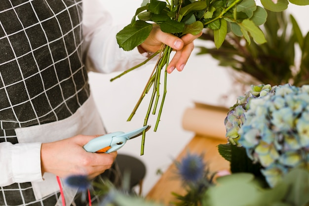 Close-up florist cutting flowers for bouquet
