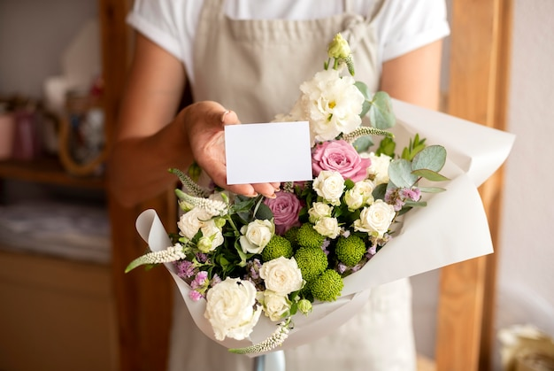 Close up florist holding bouquet and note