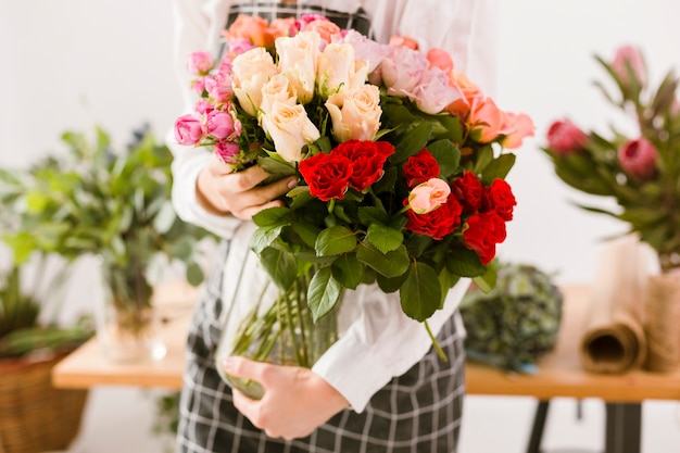 Close-up florist holding jar with flowers
