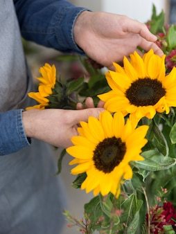 Close-up of florist touching the yellow sunflower