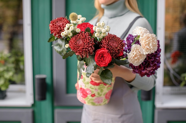 Close up of florist woman holding bunch at flower shop.