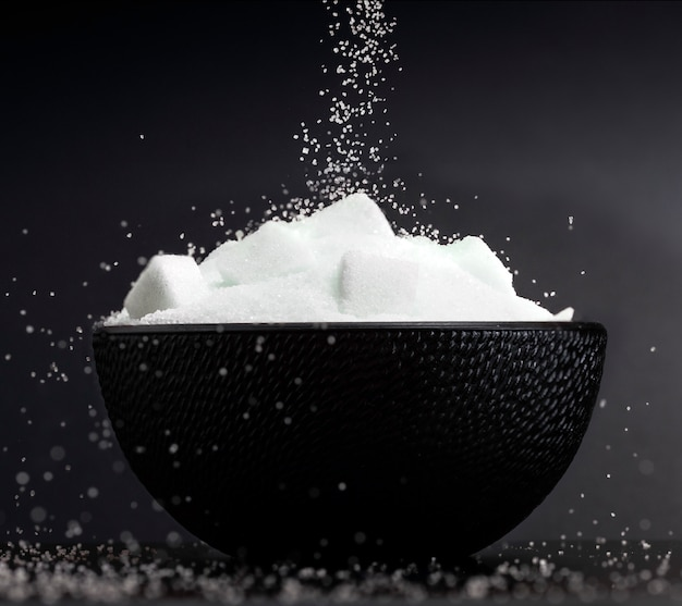 Close-up of flow of white sugar falling in a bowl with sugar cubes on black background
