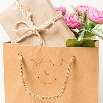 Close-up of flower bouquet and wrapped gift box in paper bag with hand drawn face on it