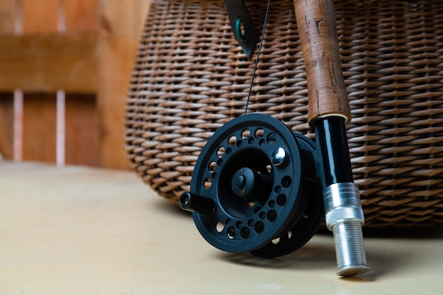 Close up of fly fishing rod with reel next to braided basket