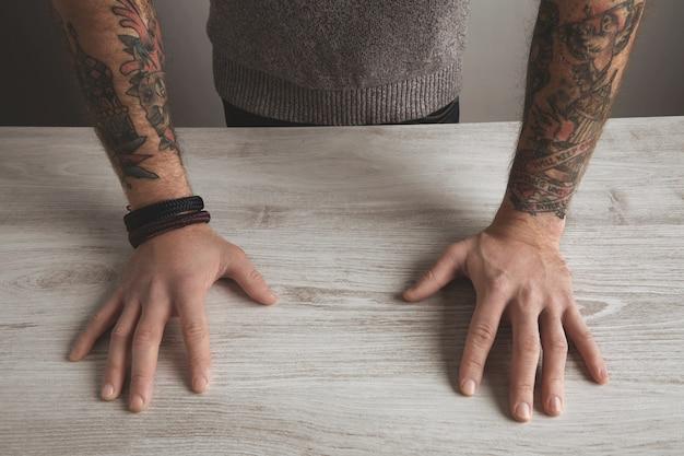 Chiuda sull'immagine dettagliata del fuoco delle mani tatuate della vecchia scuola del manicotto dell'uomo brutale irriconoscibile in maglione grigio neutro sulla tavola di legno bianca, isolata. concetto di presentazione.
