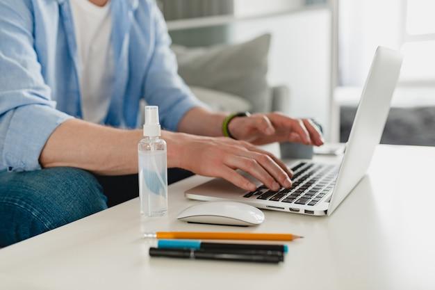Закройте фокус дезинфицирующего спрея-антисептика на рабочем месте дома, работая онлайн на ноутбуке, человек, работающий на ноутбуке