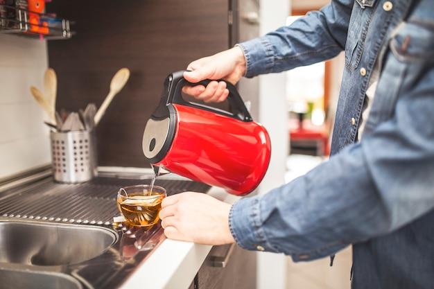 Крупным планом фокус на мужской руке, держа чайник и налив воды в чашку