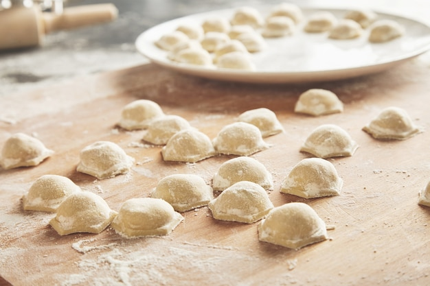 Close up focus ready tasty raviolis or dumplings filled with minced meat on flour on wooden board
