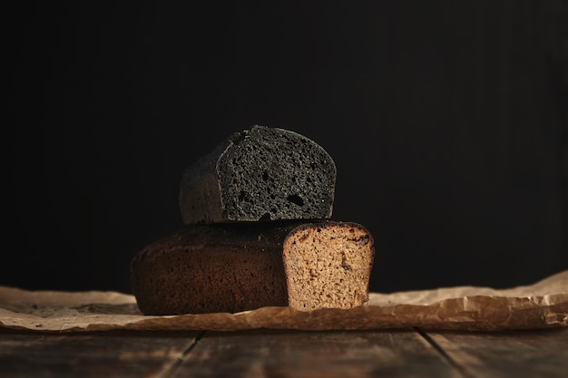 Close up focus on two freshly baked diet healthy breads. charcoal and rye with figs, isolated on black, presented on rustic wooden table