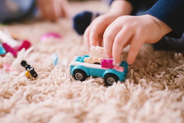 小さな男の子の手がそれを押しながらカーペットの上にプラスチックのおもちゃの車のフォーカスビューを閉じます。