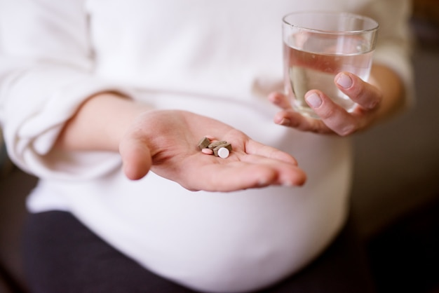 Close up focus view of the painful pregnant woman hands holding medications and glass of water.
