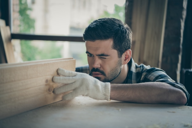 Close up  focused confident serious man measuring distance between two blocks planks with one eye closed