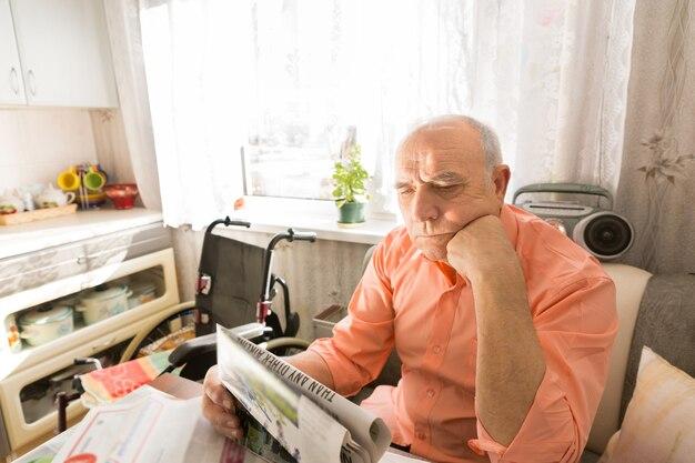 Крупным планом сфокусированный старик читает газету, сидя за своим столом в гостиной